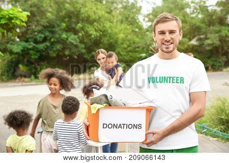 Young male volunteer holding box of donations outdoors