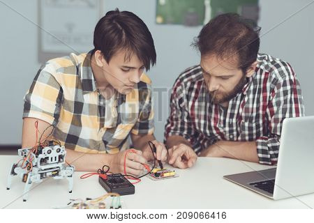 The guy and the man examine the board using a multimeter. They measure indicators. They are focused on the data. In front of them is a gray laptop