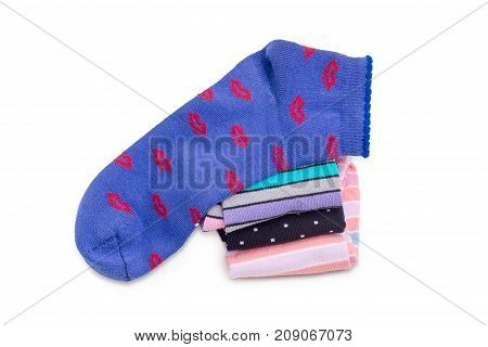 Blue women's low cut socks on a stack of other varicolored socks on a white background