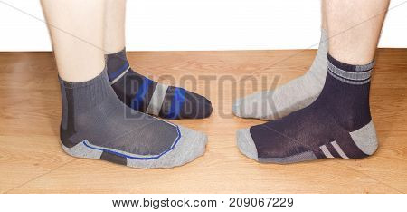 Legs of two men in different men's socks on a wooden floor on a white background