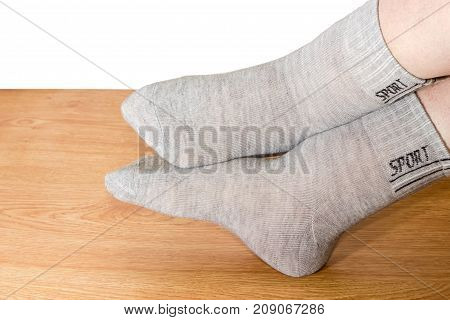 Legs of woman in the light gray socks for fitness on a wooden floor on a white background