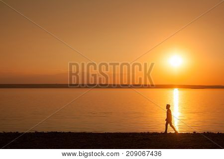 Side view of black male silhouette walking on shore of lake in bright sunset light.