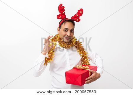 Closeup portrait of content middle-aged handsome man wearing toy reindeer horns and tinsel, looking at camera, showing OK sign and holding gift box. Isolated front view on white background.