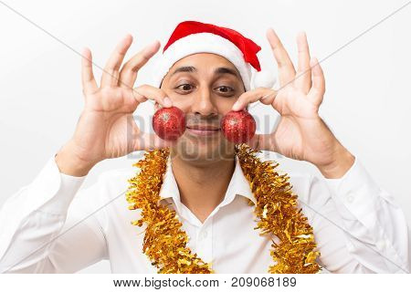 Closeup portrait of content middle-aged handsome man wearing Santa Claus hat, tinsel and holding two Christmas balls. Isolated front view on white background.