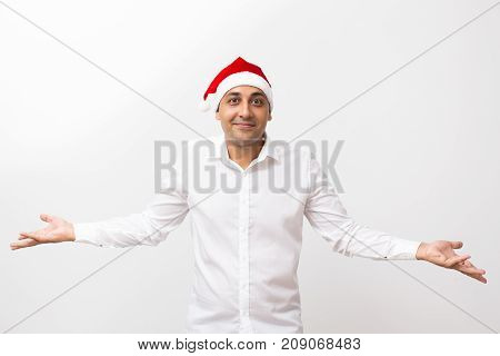 Closeup portrait of content middle-aged handsome man wearing Santa Claus hat, throwing hands up, shrugging shoulders and looking at camera. Isolated front view on white background.