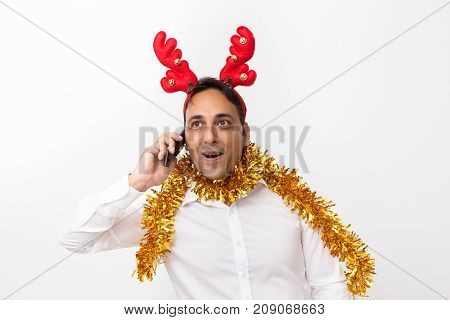 Closeup portrait of excited middle-aged handsome man wearing toy reindeer horns and tinsel, looking away and talking on smartphone. Isolated front view on white background.