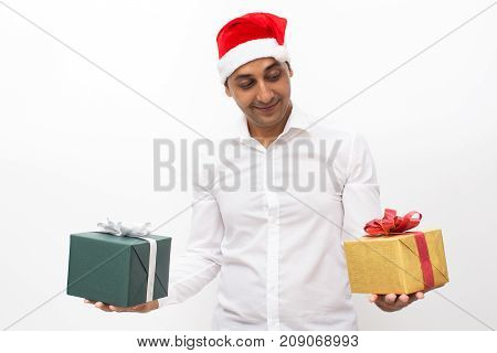 Closeup portrait of pensive middle-aged handsome man wearing Santa Claus hat, holding two gift boxes and choosing between them. Isolated front view on white background.