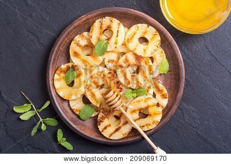 Grilled pineapple with mint and honey .