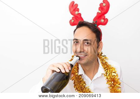 Closeup portrait of smiling middle-aged handsome man wearing toy reindeer horns, tinsel, looking at camera and drinking champagne from bottle. Isolated front view on white background.