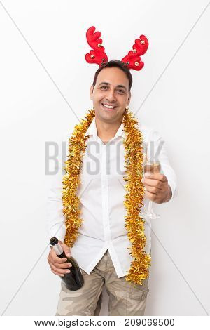 Closeup portrait of smiling middle-aged handsome man wearing toy reindeer horns, tinsel, looking at camera and holding bottle and flute with champagne. Isolated front view on white background.