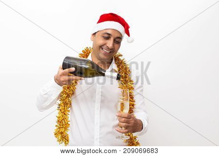 Closeup portrait of smiling middle-aged handsome man wearing Santa Claus hat, tinsel and pouring champagne into flute from bottle. Isolated front view on white background.