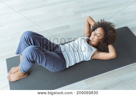 Top view full length cheerful mulatto girl doing abdominal crunches on mat in apartment. Sport concept. Copy space