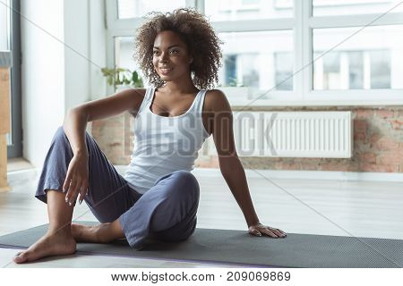 Portrait of full length outgoing african female having break after exercising on floor in room. Copy space