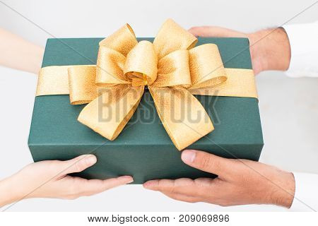 Beautiful packaged Christmas gift with yellow ribbon in hands of couple. Friends celebrating New Year and giving gift. Gift box with bow. Presenting gift concept
