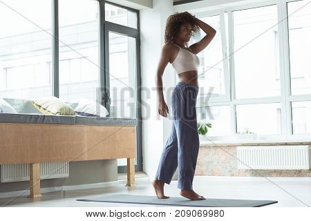 Full length cheerful mulatto woman with curly hair standing on mat while taking exercise in apartment