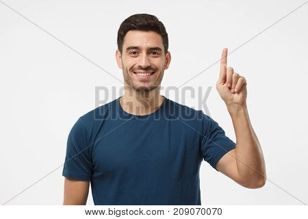 Attractive Young Man In Blue T-shirt Pointing Up With His Finger Isolated On Gray Background