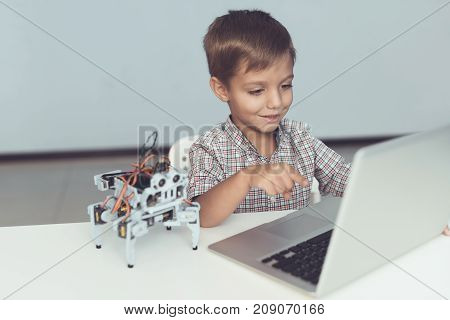 Close up. A little boy is sitting at a table and working behind a gray laptop. Nearby is a small robot, which watches the work of the boy. The boy is smiling