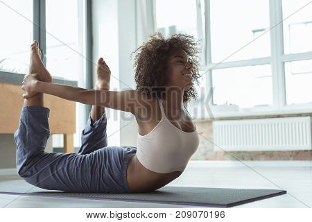 Full length side view beaming mulatto girl practicing exercise on mat in modern room. Copy space