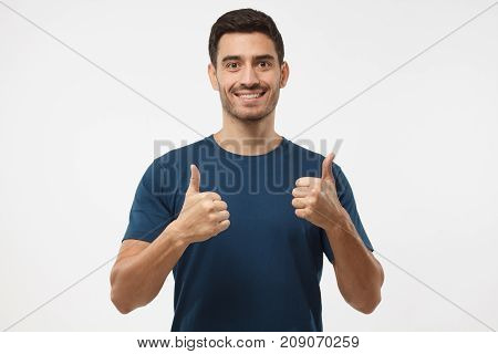 Closeup Of Young Optimistic Man Isolated On Grey Background Showing Thumps Up With Positive Emotions