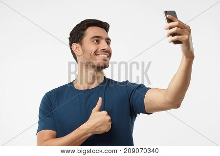 Photo Of Handsome Male Isolated On Grey Background, Stretching Arm With Smartphone To Take Selfie Pi