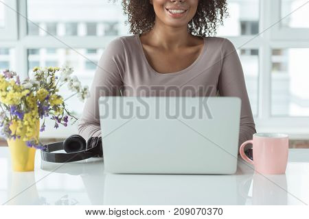 Outgoing mulatto girl having job on laptop while situating at desk in office