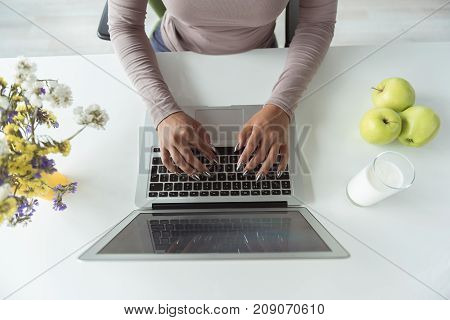 Top view close up of female arms typing on keyboard of new notebook computer. She sitting at table