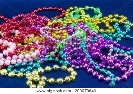 Green, Purple, And Gold Mardi Gras Beads Isolated On Blue