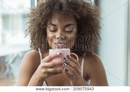Portrait of beaming young african girl drinking cup of delicious coffee in room