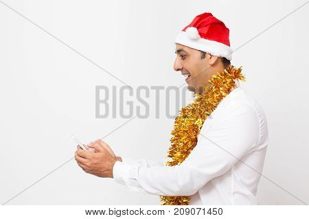 Thrilled manager in Santa Hat reading sms on phone or waiting for message about sale. Cheerful excited young Indian man with tinsel on neck reading shocked news on Internet. Christmas discount concept