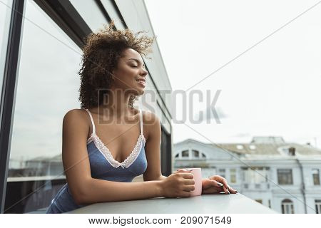 Side view cheerful mulatto girl drinking cup of appetizing coffee while standing on balcony. Copy space