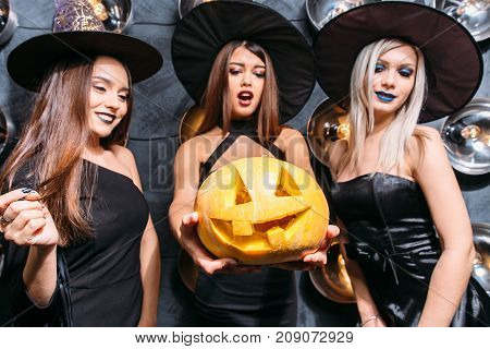 Three Cheerful Young Women In Witch Halloween Costumes With Pumpkin