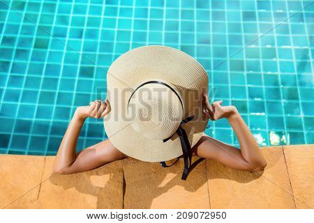 Bikini woman in pool relaxing young asian beautiful sexy female resting in vacation on summer season with hat at resort swimming pool