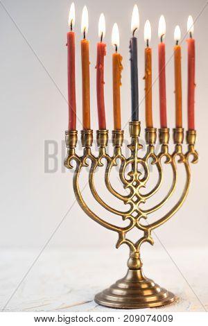 Brass hanukiya with lighted candles close-up vertical