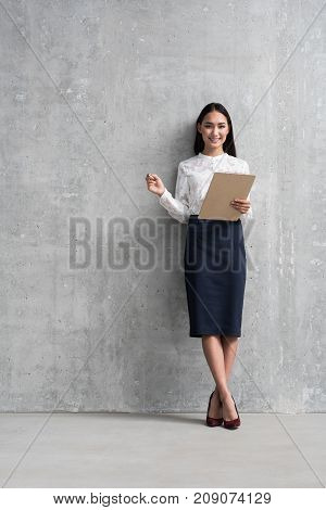 Full length portrait of beaming asian businesswoman keeping clipboard while leaning against door. Copy space. Job concept