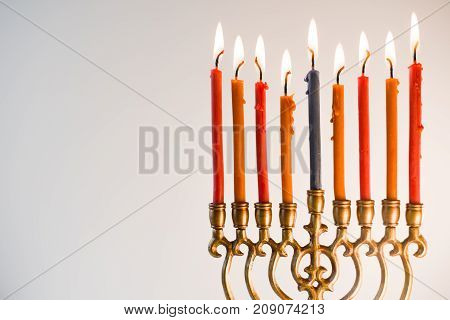 Brass hanukiya with lighted candles close-up horizontal