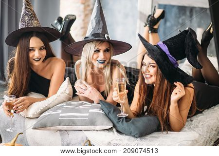 In Good Moods At Halloween Party. Womans Lying And Drink Champagne