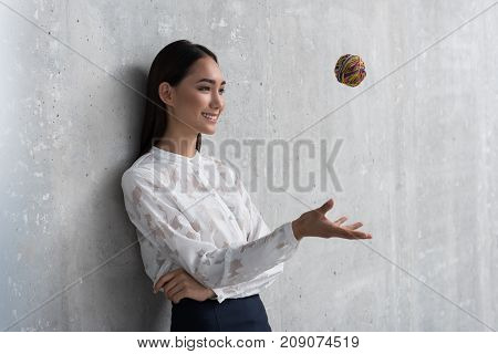 Side view beaming young asian career woman throwing small colorful ball. Enthusiasm concept. Copy space