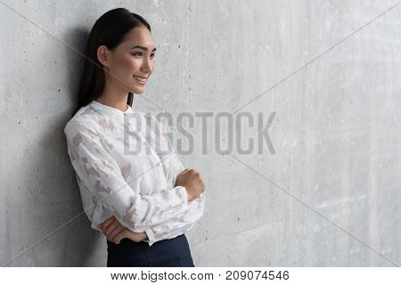 Side view outgoing businesswoman with crossing arms leaning against concrete wall. Occupation concept. Copy space