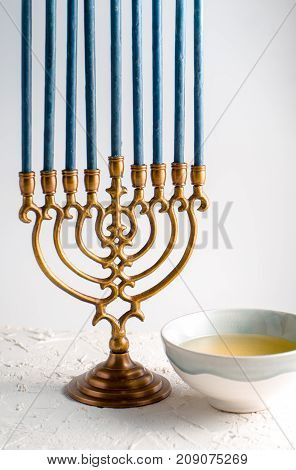Menorah brass Hanukkah with blue candles and butter in a bowl vertical