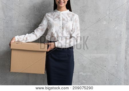 Smiling young asian career girl keeping big carton in hand. Delivery concept. Copy space