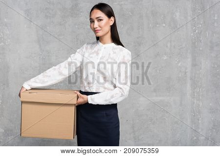 Portrait of outgoing businesswoman holding cardboard box in arms. Copy space. Movement concept