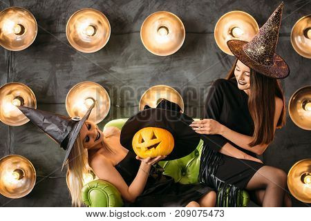 three happy young women in black witch halloween costumes having fun on party