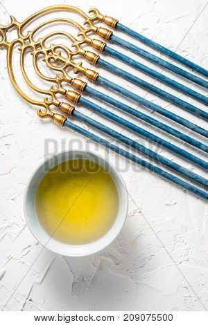 Menorah brass Hanukkah with blue candles and butter in bowl top view vertical