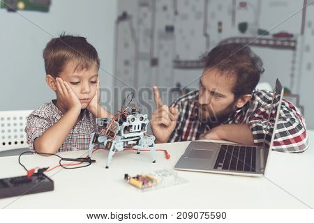 The boy hurt the robot. A man severely chastises the boy, explaining to him his mistakes. The boy is sitting at the table in front of the laptop. the man sat down next to the boy