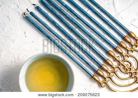 Brass Hanukiya Menorah with blue candles and butter in a bowl diagonal horizontal