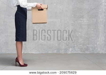 Close up legs of young businesswoman in formal clothes holding cardboard box in arms. Loose job concept. Copy space