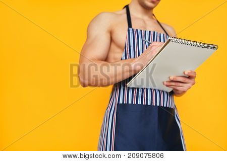 Crop muscular man wearing apron while posing shirtless and taking notes on notebook.