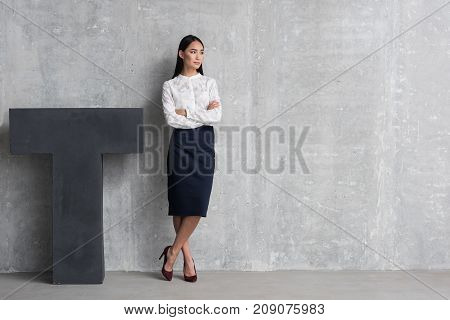 Full length portrait of serene young lady with crossing arms locating near big T. Copy space