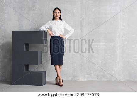 Executive. Full length portrait of serene asian woman in formal wear standing near huge letter. Copy space