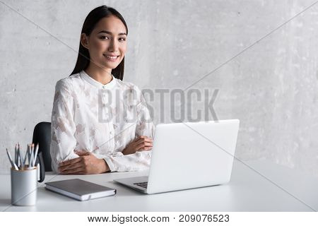 Cheerful asian woman is locating at workplace and looking ahead with wide smile. Open laptop on desk. Portrait. copy space on right side